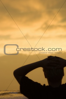 Boy relaxing on beach at sunset