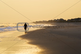 Boy walking on beach at sunset
