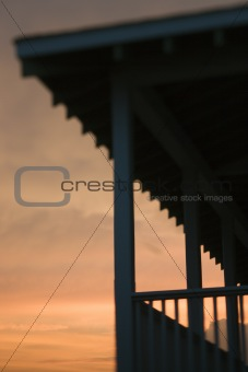 Beachfront porch silhouetted at sunset