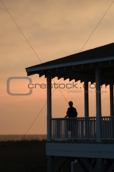 Boy on beachfront porch silhouetted at sunset