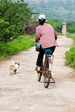 Woman on Bicycle with Dog