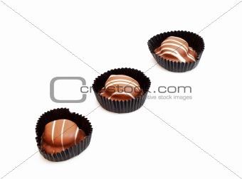 Three chocolate candies on white background