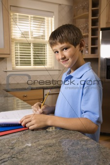 Boy doing homework at kitchen counter.