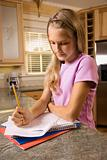 Girl doing homework at kitchen counter.