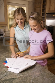 Mom helping daughter with homework at kitchen counter.