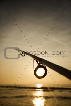 Fishing pole against ocean at sunset.