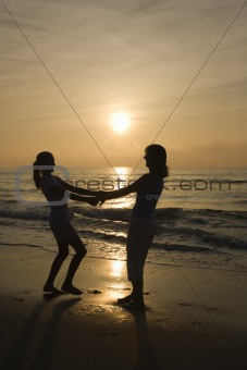 Mom and daughter spinning in circle at sunrise.
