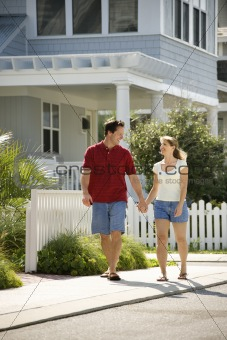 Couple walking on sidewalk.