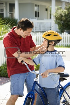 Dad helping son with bicycle helmet.