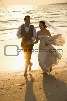 Bride and groom running down beach.