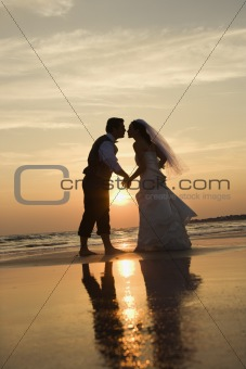 Bride and groom kissing on beach.