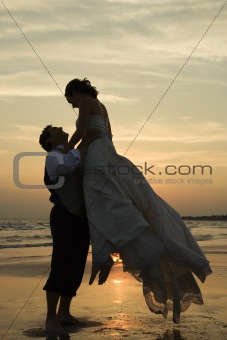 Groom lifting bride up at beach.