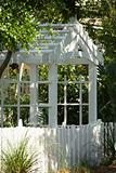 Garden arbor with white picket fence.