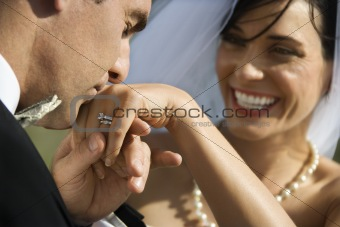 Groom kissing hand of smiling bride.
