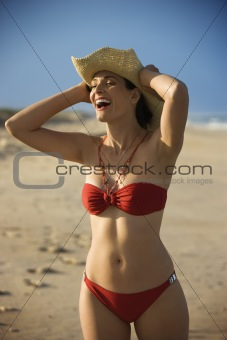 Woman in bikini holding hat.