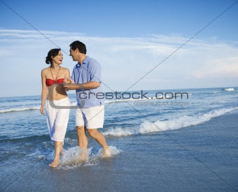 Couple walking in waves.
