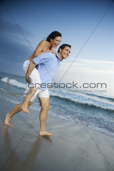 Man carrying woman piggyback at beach.