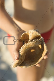 Woman holding conch shell.