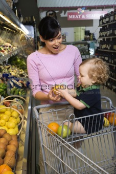 Mother grocery shopping with toddler.