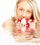happy blond in water with red and white petals