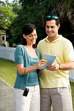 Couple holding map and smiling.