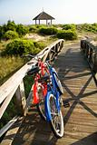 Bikes leaning against wooden railing.