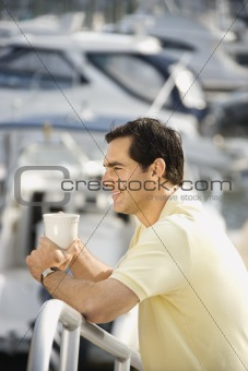 Man holding coffee cup at harbor.