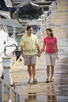 Couple holding hands and walking at harbor.