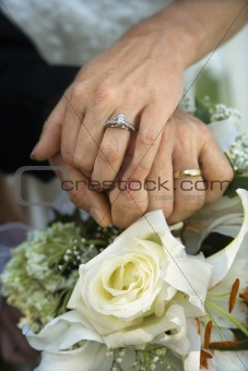 Bride and groom's hands overlapping.