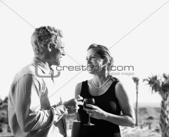Caucasian couple holding wine glasses.