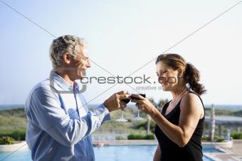 Caucasian couple toasting wine glasses.