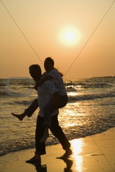 Man carrying woman on beach at sunset.