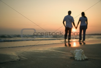 Couple holding hands on beach.