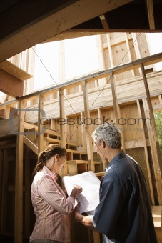 Caucasian man and woman on construction site.