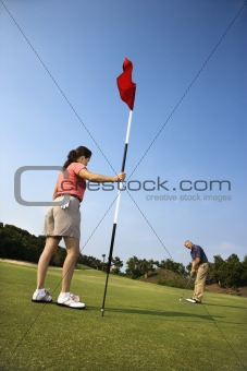 Man putting at golf course with womann holding flag.
