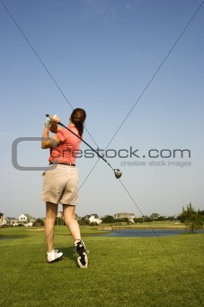 Woman swinging golf club.