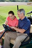 Smiling couple in golf cart on golf course.