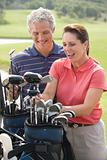 Smiling couple playing golf