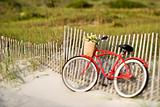 Bike leaning against fence at beach.