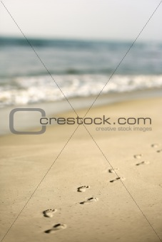 Coastline with footprints and waves.