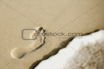 Footprint in sand next to wave.