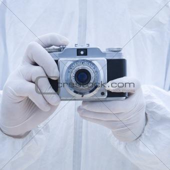 Man in biohazard suit holding antique camera.