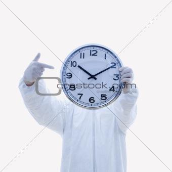 Man in biohazard suit holding clock.