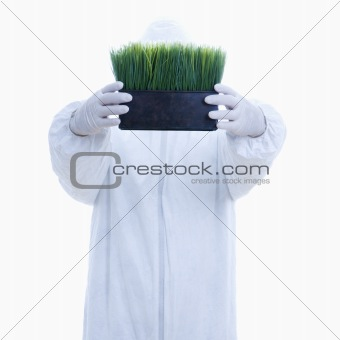 Man in biohazard suit holding pot of grass.