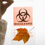 Gloved hand holding  biohazard bag.