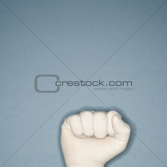 Fist wearing rubber glove.