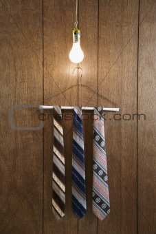 Three retro ties on hanger beneath lightbulb.
