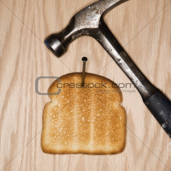 Slice of toast nailed to wood with hammer.