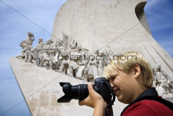 Caucasian boy with camera at the Monument to the Discoveries in