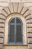 Arched window with closed shutters in Rome, Italy.